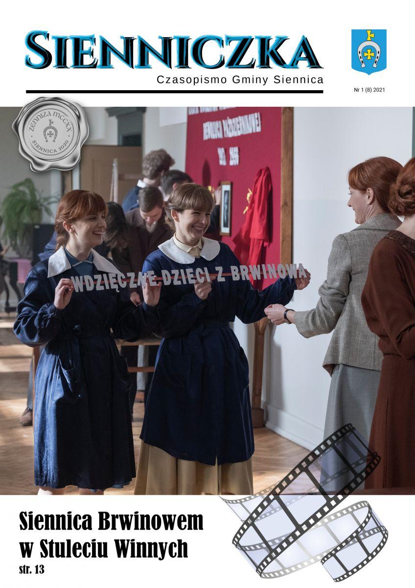 Sienniczka czasopismo gminy Siennica. Dwie uczennice trzymają w ręku tabliczkę z napisem Wdzięczne dzieci z Brwinowa. W tle korytarz szkolny.